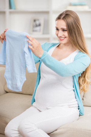 Beautiful pregnant woman sitting at sofa and holding creepers. Stock Photo