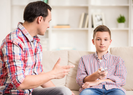 Boy sitting at sofa and watching television while his father talking to him. photo
