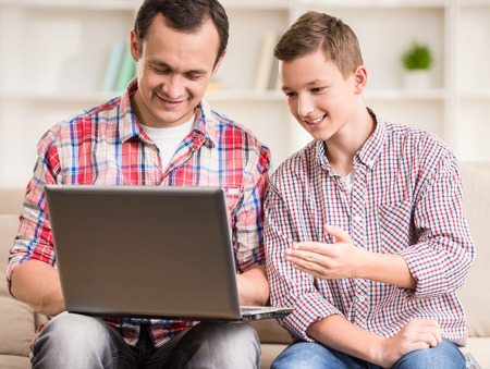 boy sitting: Father and son using laptop together at home. Stock Photo