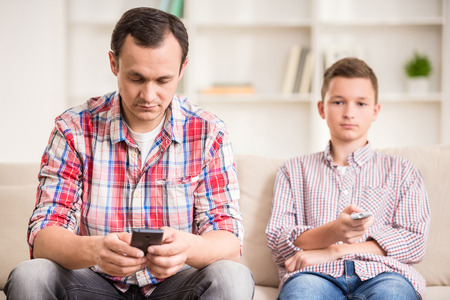Boy sitting at sofa and watching television while his father using his phone.