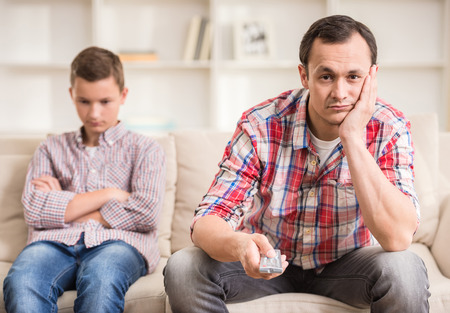 man sad: Boy sitting at sofa and get bored while his father watching television.