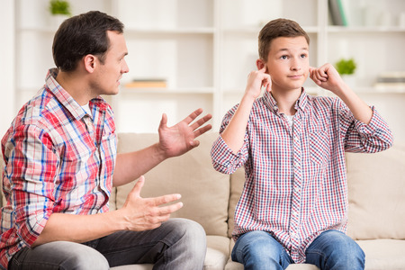 male parent: Son closing ears while father scolding  him. Stock Photo