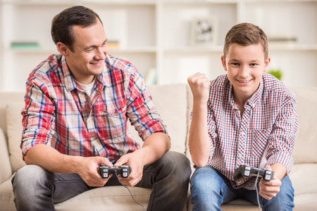 game room: Father and son dressed casual having fun at home while playing computer games.
