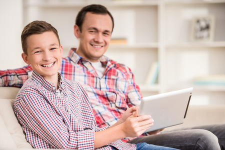 young boy smiling: Boy sitting at sofa at home with father and using laptop. Stock Photo