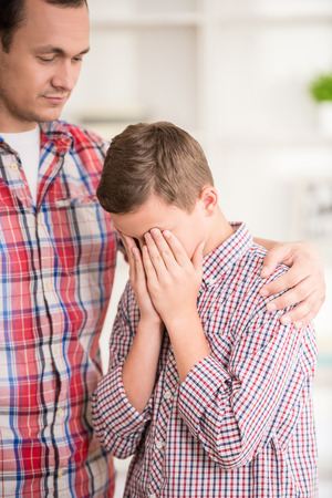 scold: Boy crying while father scold him. Family quarrel.