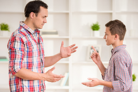 arguing: Father and son dressed casual having quarrel at home. Stock Photo