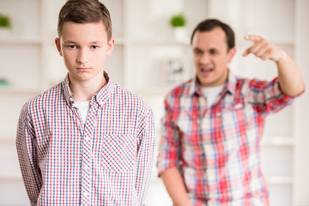 personne en colere: Père et fils habillés casual ayant querelle à la maison.