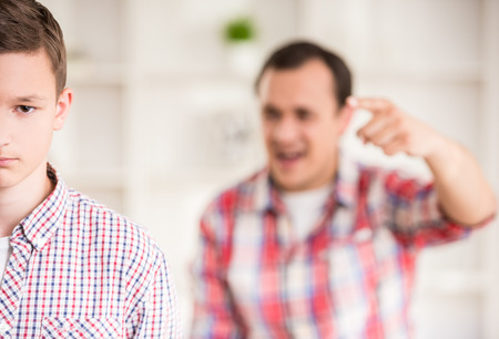 bad guy: Father and son dressed casual having quarrel at home. Stock Photo