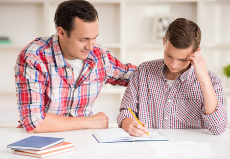 homework: Happy father helping his son to do homework.