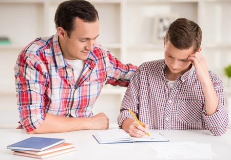ayudando: Padre feliz ayudando a su hijo a hacer la tarea. Foto de archivo