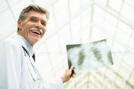 Mature male doctor looking at X-ray. Healthcare and medicine concept. photo