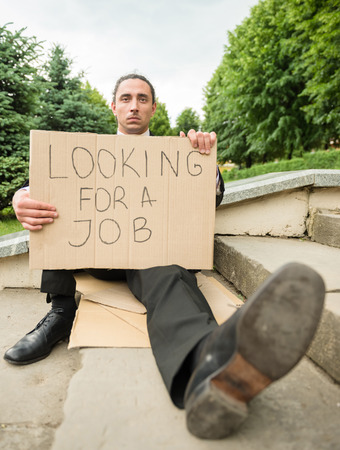 looking for job: Man in suit sitting at stairs with sign. Unemployed man looking for job.