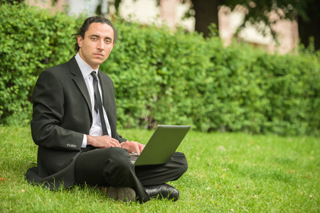 looking for job: Man in suit sitting at lawn with laptop. Unemployed man looking for job. Stock Photo