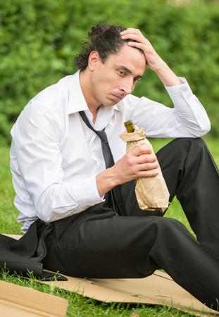 tomando alcohol: Frustrado hombre desempleado que se sienta en el c�sped y el consumo de alcohol. Depresi�n.