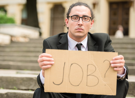 looking for job: Man in suit sitting at stairs with sign in hands. Unemployed man looking for job.