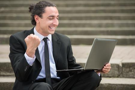 Man in pak zittend op de trap met laptop. Werkloze man op zoek naar werk. Stockfoto