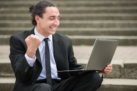 looking for job: Man in suit sitting at stairs with laptop. Unemployed man looking for job. Stock Photo