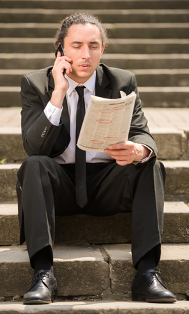 looking for job: Man in suit sitting at stairs with newspaper. Unemployed man looking for job.