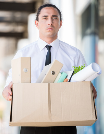 unemployed dismissed: Fired frustrated man holding box with files ar office.