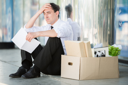 work out: Fired frustrated man in suit sitting near office. Stock Photo