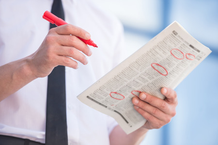 Close-up of unemployed man in suit reading newpaper outdoors. Stockfoto