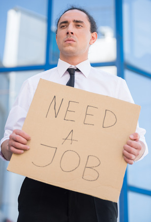 looking for job: Man in suit holding sign in hands. Unemployed man looking for job. Stock Photo