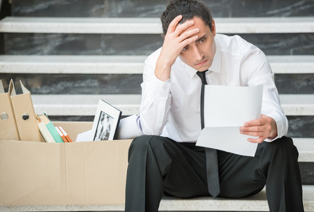 dismissed: Fired frustrated man in suit sitting at stairs in office.
