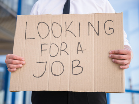 looking for job: Close-up of man in suit holding sign in hands. Unemployed man looking for job.