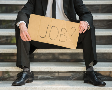 looking for job: Close-up of man in suit sitting at stairs with sign in hands. Unemployed man looking for job.