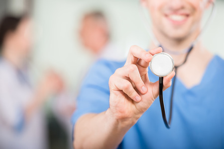 Close-up of smiling doctor with stethoscope with colleagues on background. Stock Photo