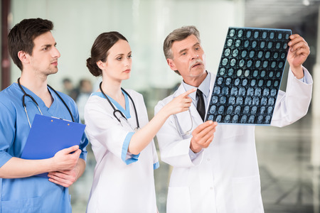 brain disease: Group of doctors looking at X-ray at offie. Stock Photo