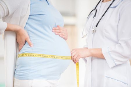 Close-up of female doctor measuring the tummy of her pregnant patient ar clinic.