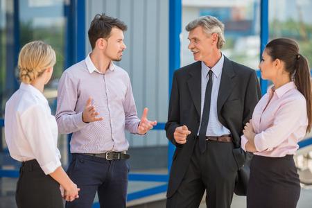 empleados trabajando: Grupo de personas exitosas en trajes de pie delante de la oficina y discutir la estrategia de negocio.