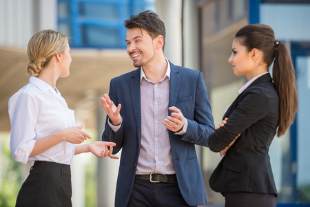 sales occupation: Three successful business people in suits discussing project outdoors. Office background. Stock Photo
