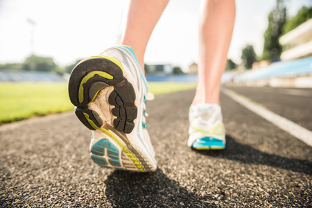foots: Close-up of female foots in sneakers. Sporty woman running outdoors at sunrise.