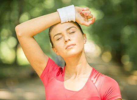 sudando: Primer plano de una mujer joven deportivo después del entrenamiento al aire libre en la mañana. Foto de archivo