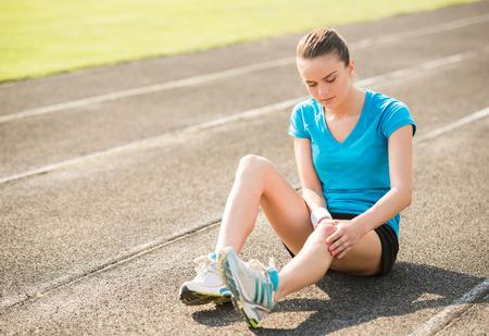 de rodillas: Mujer corredor atleta tocar pie en el dolor debido a esguince de tobillo. Foto de archivo