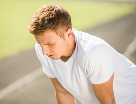 Young sporty man prepares to run sprint. Training outdoors at sunrise.