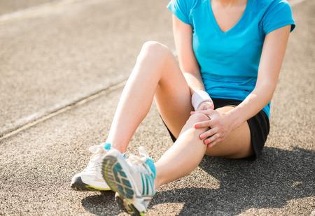 女性アスリート ランナーの足関節捻挫による痛みの足に触れます。