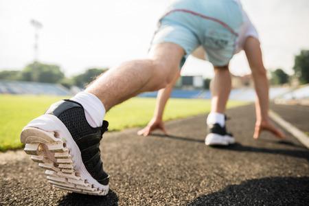 hombres corriendo: Primer plano de hombre deportivo listo para correr sprint. Atleta masculino en la poderosa línea de salida plantean.