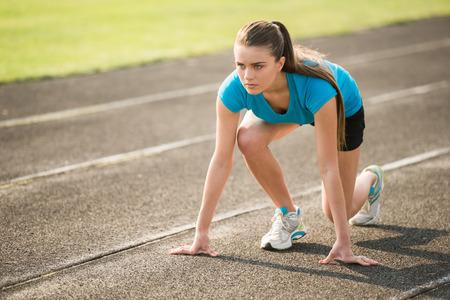 Aantrekkelijke sportieve meisje klaar om sprint lopen. Vrouwelijke atleet in krachtige startlijn opleveren.