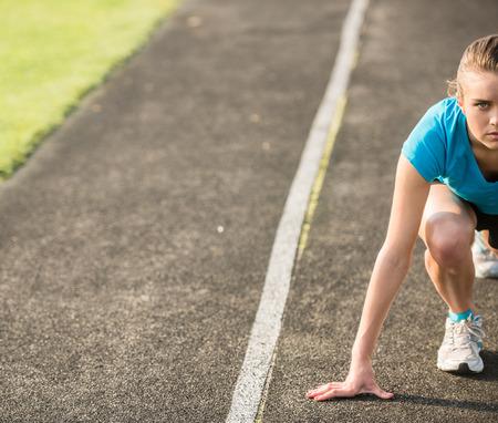 Attractive fille sportive prêt à fonctionner sprint. Athlète féminine dans puissante ligne de pose de départ. Banque d'images - 41672918