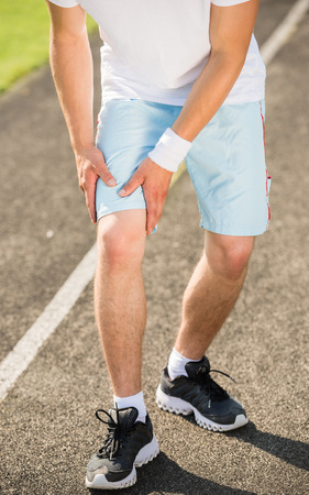 sprained joint: Closeup of young sporty man prepares to run sprint.