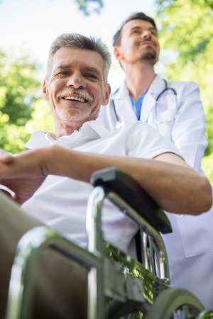 garden staff: Male nurse walking with senior patient in wheelchair in garden near hospital.