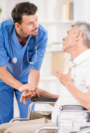 white person: Male nurse talking with senior patient in wheelchair.