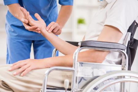 enfermeras: Enfermera de sexo masculino que toma el pulso del paciente mayor en el hospital. Foto de archivo