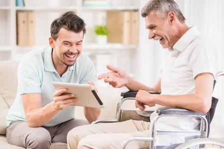 Sonriente hombre guapo cuidando de su padre eldery en silla de ruedas.