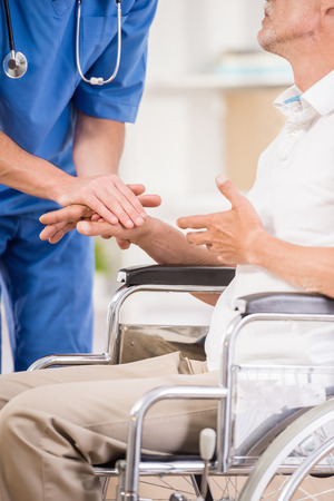 two person: Male nurse talking with senior patient in wheelchair.