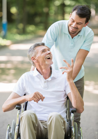 Adult son walking with disabled father in wheelchair outdoor. Front view.