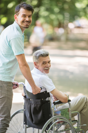 frailty: Adult son walking with disabled father in wheelchair at park.